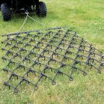 A chain harrow being used to flatten a large lawn.